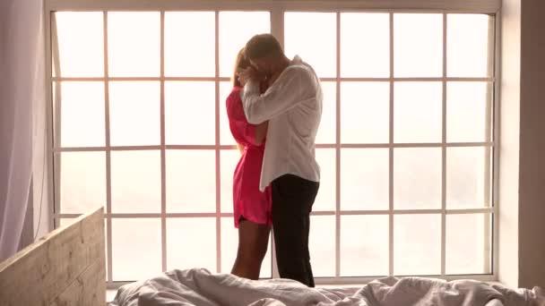 年轻的夫妇在卧室里亲吻