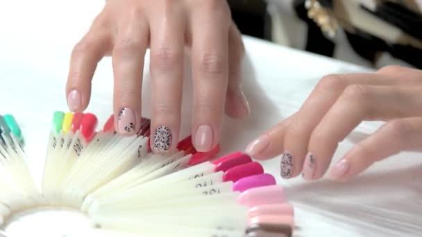 Sanfte Frauenhände bei der Farbwahl.