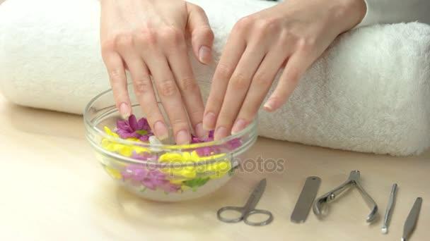 Krásné ženské ruce v aroma koupele.