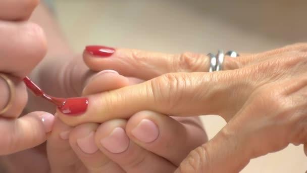 Manikérka maluje nehty ženy.
