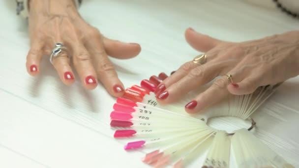 Rukou aristokratické žena s červeným manikúra.