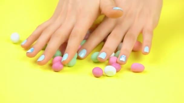 Pěstěné ruce a vícebarevné karamelové bonbóny.