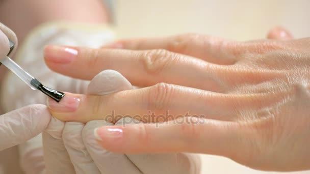Žena přijímá manikúra v salonu krásy
