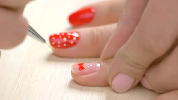 Manicurist drawing a heart on female nails.