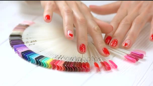 Volba barvy nehtů ženských rukou.