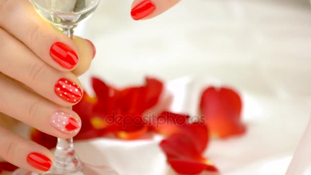 Manicured hands with champagne glass.