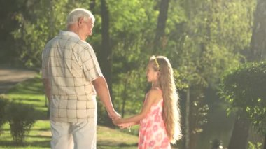 Grandfather talking to his granddaughter in the park.