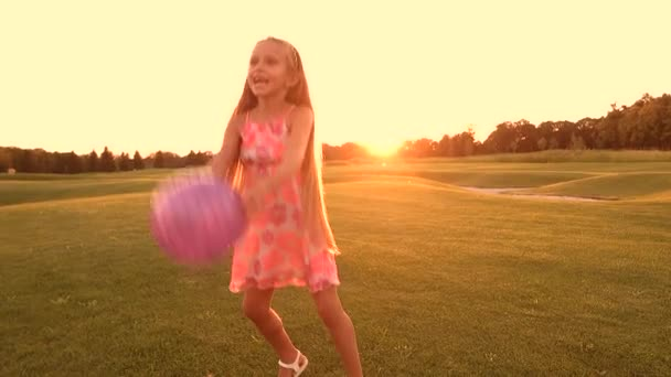 fröhliches Kind spielt mit Ball im Freien.