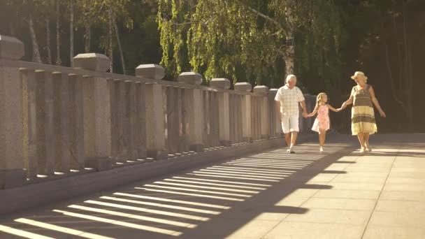 Cute girl walking with grandparents.