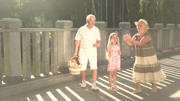 Granddaughter and grandparents having fun outdoors.