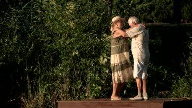 Cute couple of seniors dancing outdoors.