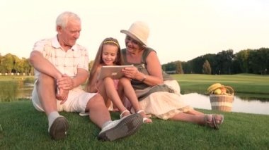 Girl with grandparents holding pc tablet.