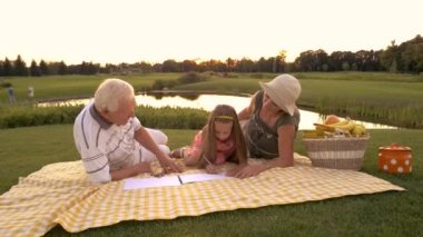 Grandparents drawing with granddaughter outdoors.