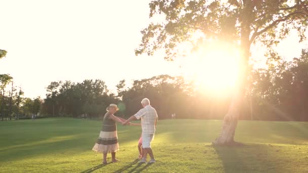 Grandparents and grandchild having fun in park.