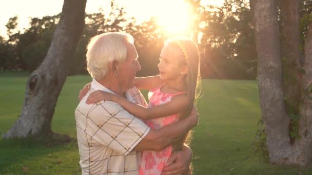Conversation between grandpa and granddaughter outdoors.