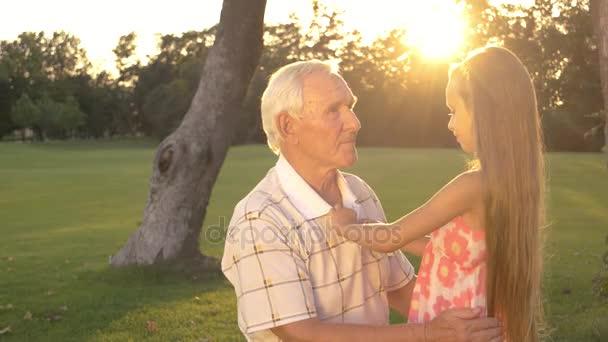 Opa und kleines Mädchen reden draußen.
