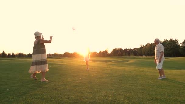 Nagyszülők és a lány játszik labda szabadban.