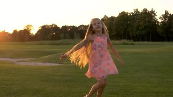Roztomilá holčička tančí na trávě.