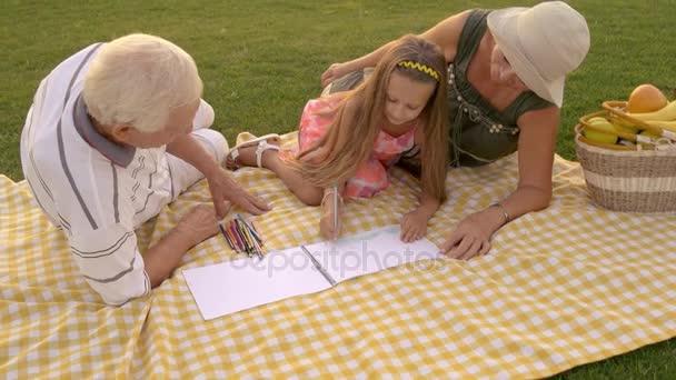 Dívka s prarodiči kreslení venku