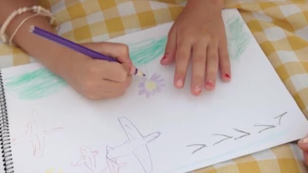 Színes ceruzával kislány kezében.