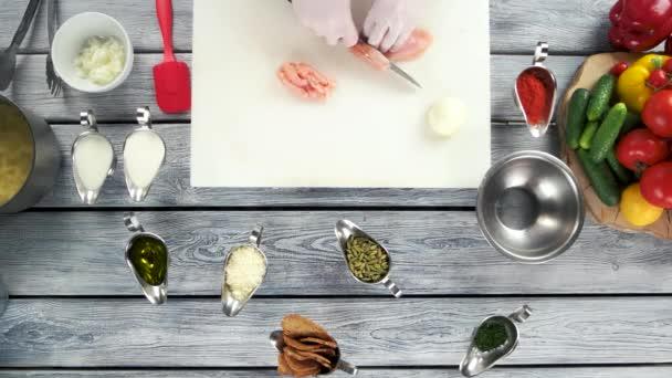 Hands cutting raw chicken breast.