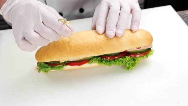 Kezében a séf, szendvics.