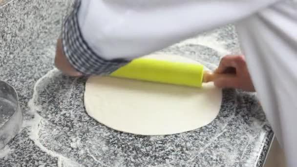 Hands rolling dough.