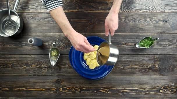 Chef pouring sauce on ravioli.