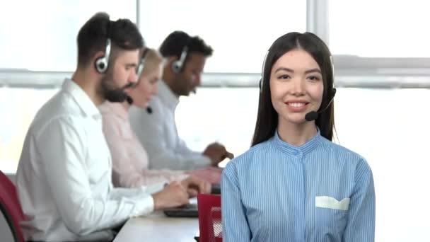 Asijská dívka v kanceláři chválí její kolegové.