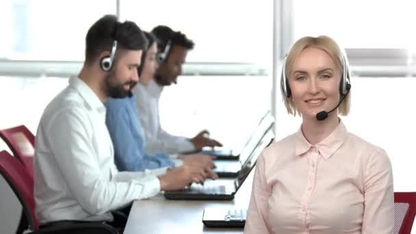 Blonďatá žena s mikrofonem s úsměvem v úřadu