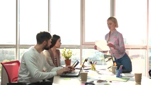 Veselá lady ukazující papíru s kolegy v kanceláři.