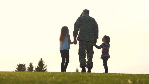 Soldato di vista posteriore in uniforme a piedi con le figlie