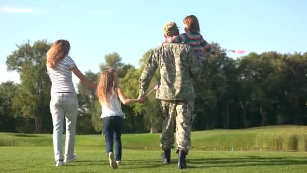 Soldato e la sua famiglia andando verso il lago
