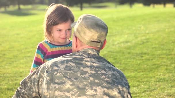Soldato in camoubackgrounde che abbraccia la sua figlia nel parco