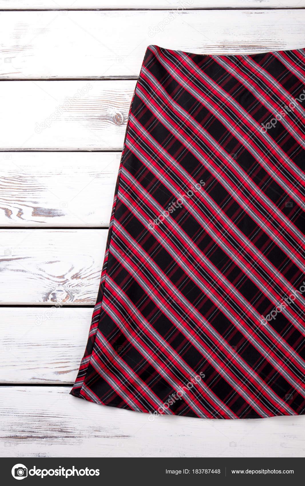 d9bd80ff18 Falda rayas rojo clásico. Mujer falda colores sobre fondo blanco de madera.  Ropa de moda femenina — Foto de Denisfilm