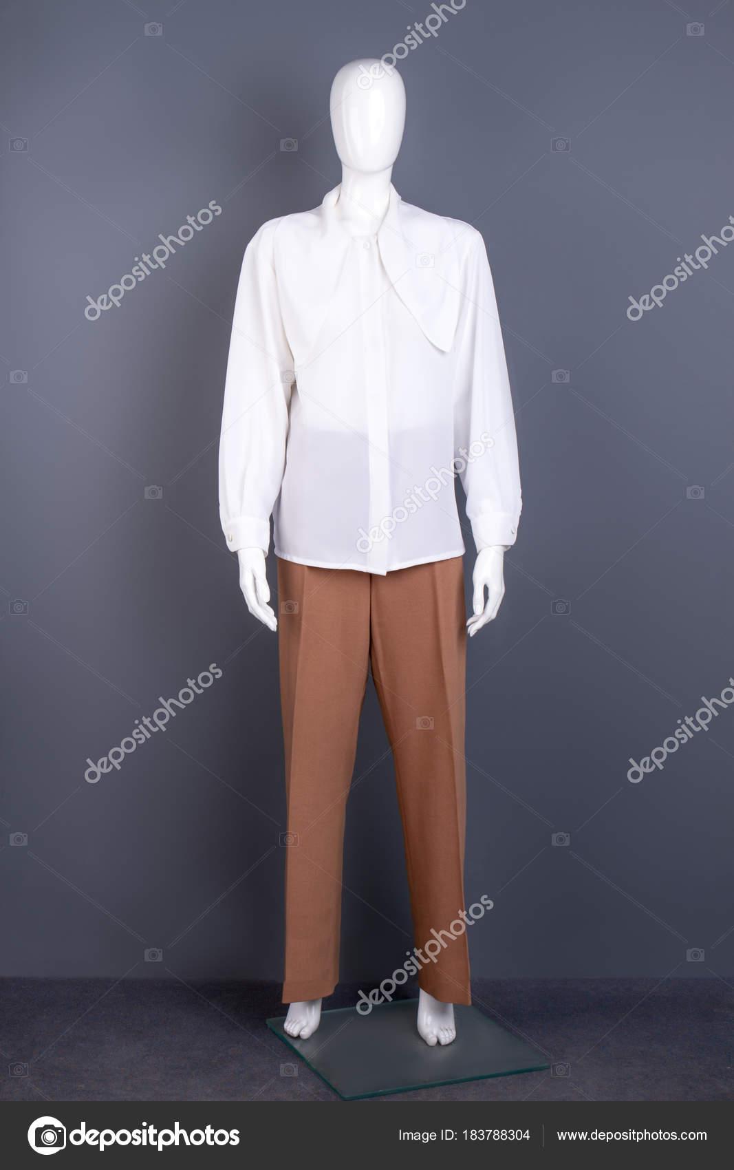 71a374c22e1e Γυναικών λευκό πουκάμισο Σιφόν σε μανεκέν. Πλήρες μήκος ανδρεικέλου  ντυμένοι με μακριά μανίκια μπλούζα και παντελόνι καφέ