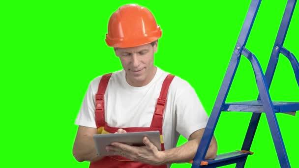 Worker in helmet with computer tablet.