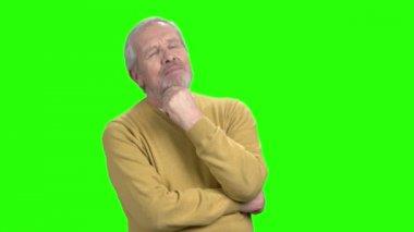 Pensive mature man on green screen.