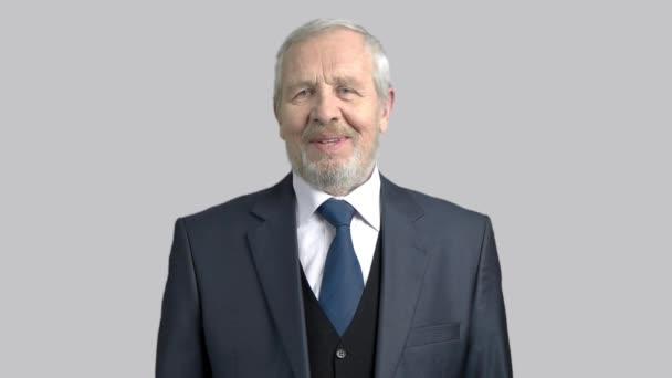 Boldog szakállas üzletember, szürke háttér