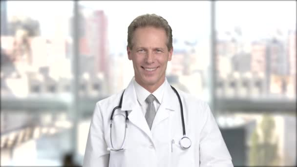 Cheerful male doctor gesturing thumb up.
