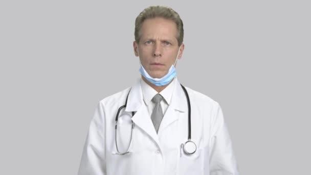 Strach starší lékař, šedé pozadí.