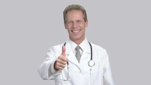 Happy kavkazské doktor ukazuje palec.
