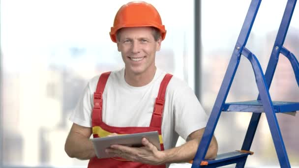 Happy mature builder with pc tablet.