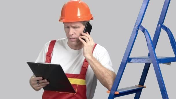 Seriöser Bauarbeiter mit Handy.