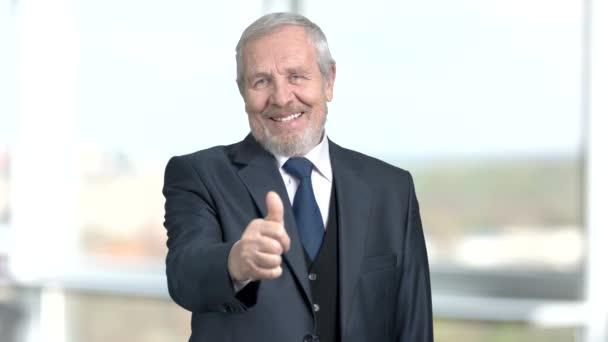 Handsome elderly boss gesturing thumb up.