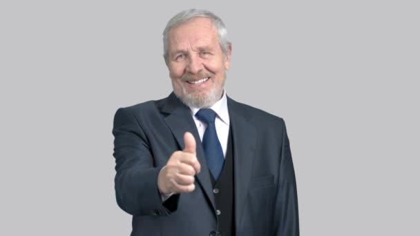 Handsome old businessman gesturing thumb up.