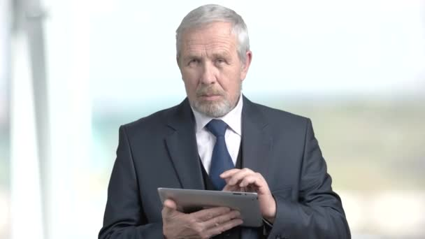 Elderly businessman working on pc tablet.