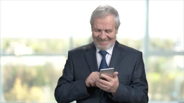 Elderly smiling businessman using smartphone.