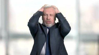 Mad elderly businessman, blurred background.