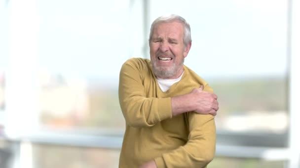 Uomo senior che soffre dal dolore alla spalla